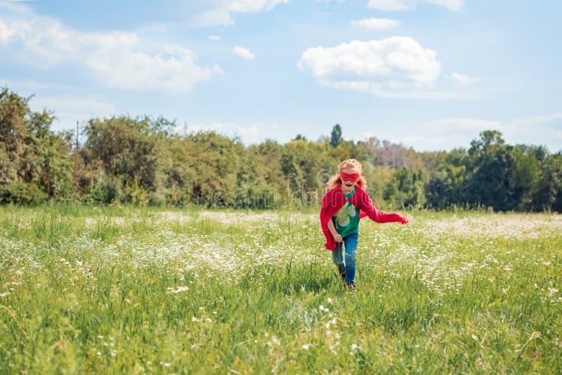 criança no traje vermelho do super-herói que corre no prado imagens de stock