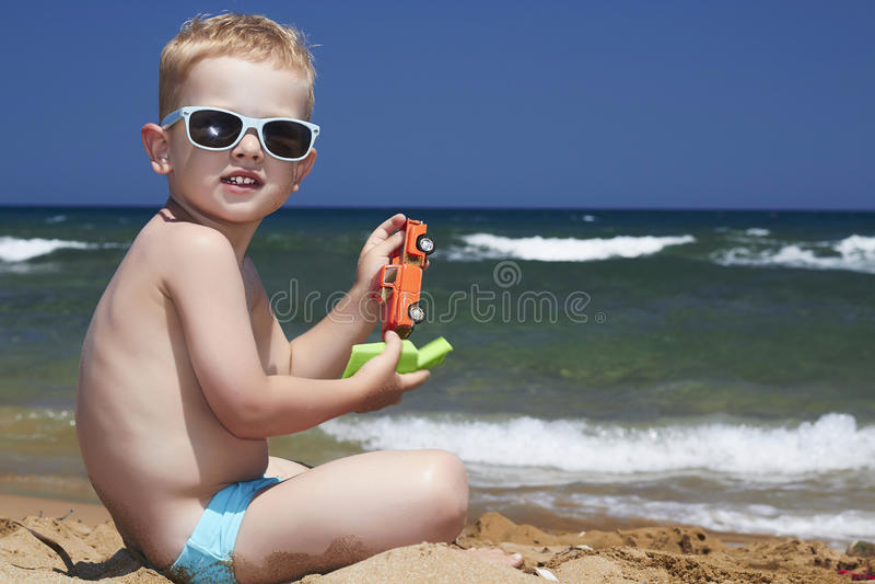 Criança nos óculos de sol na praia. rapaz pequeno próximo  imagem de stock