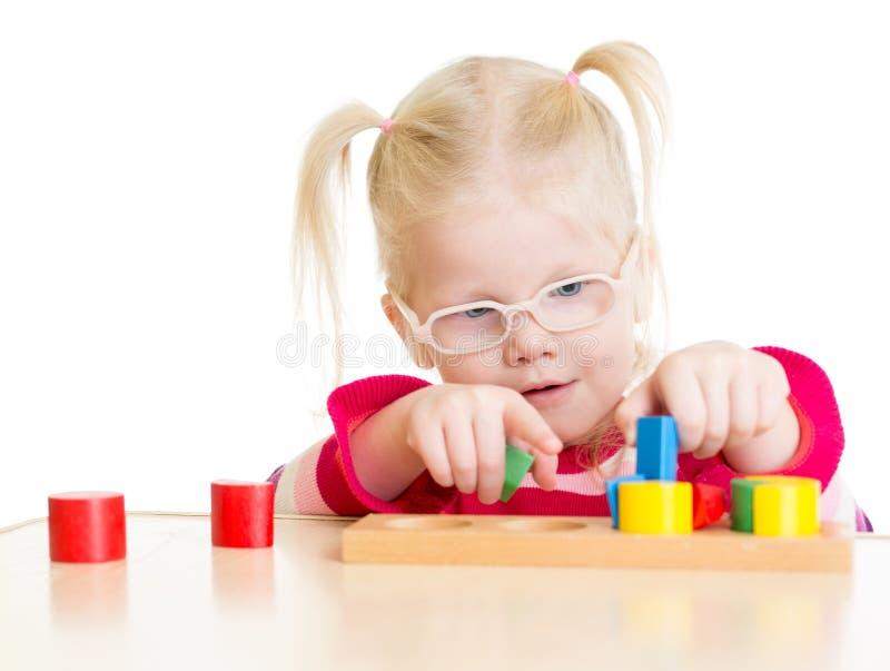 Criança nos eyeglases que jogam o jogo lógico isolado imagens de stock