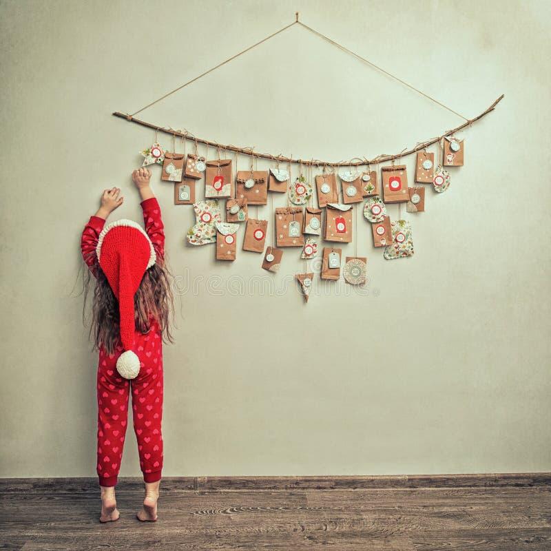 A criança nos pijamas e no tampão do Natal estica para o calendário do advento com presentes pequenos a criança conta dias até o  imagens de stock royalty free