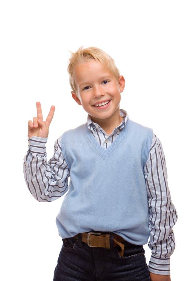 A criança nova é feliz e mostrando a vitória fotografia de stock