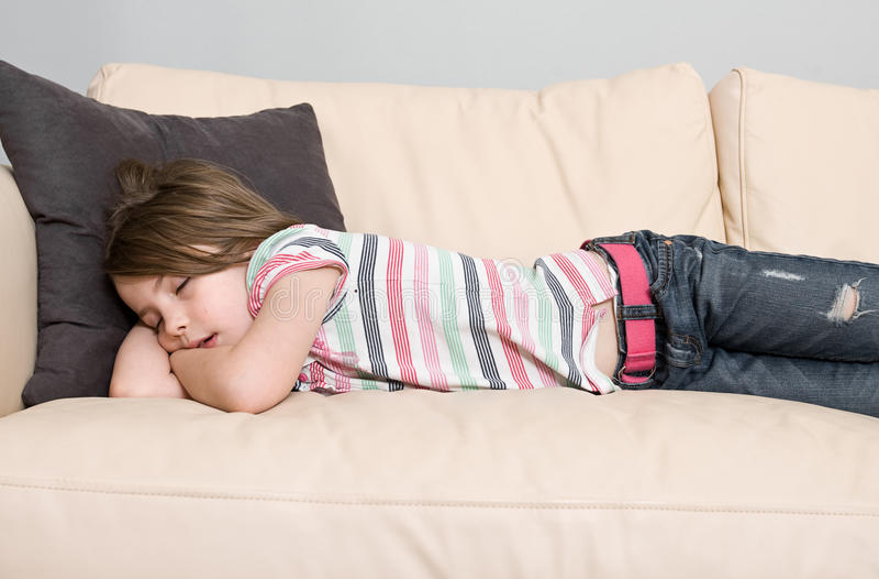 Criança nova adormecida em um sofá de couro fotografia de stock royalty free