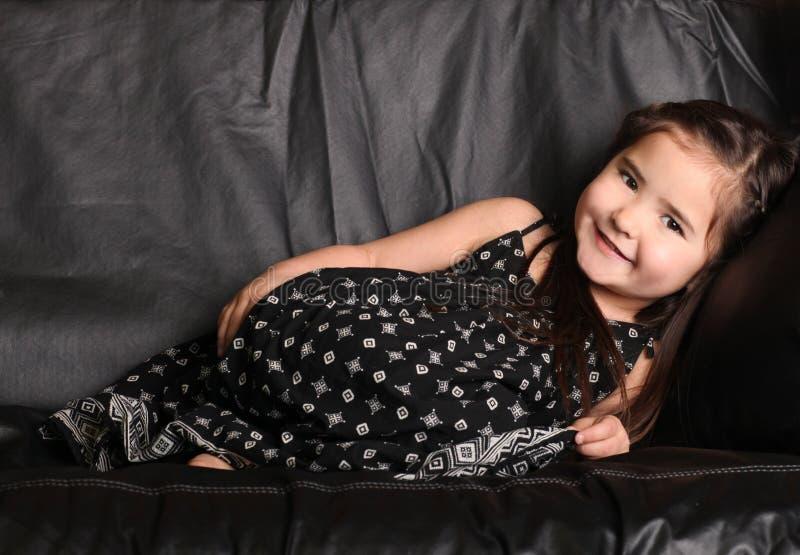 Criança nova bonito que encontra-se em um sofá imagens de stock royalty free