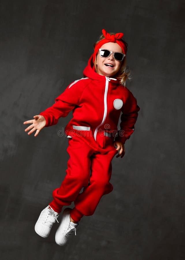 Criança nova do bebê que salta no pano e em óculos de sol vermelhos na parede cinzenta escura imagens de stock royalty free
