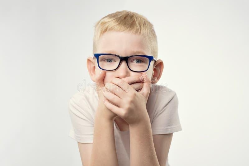 A criança nova do menino mostra o gesto de mão do sinal que guarda o dedo nos bordos imagens de stock royalty free