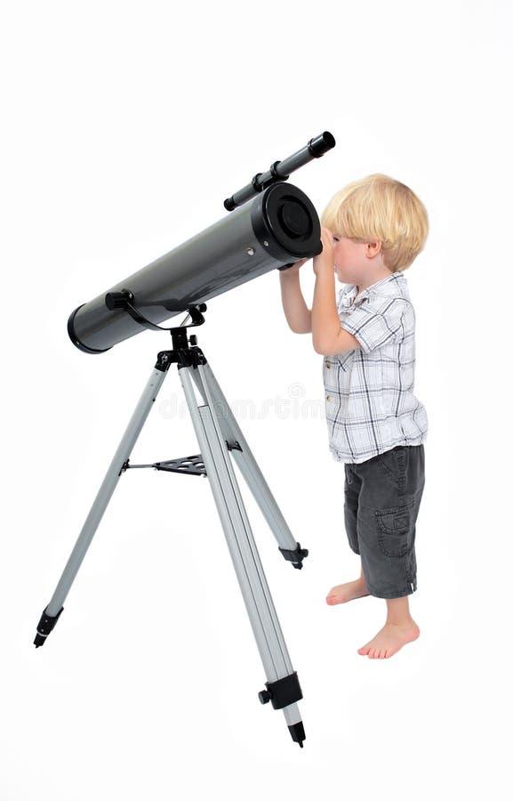 Criança nova ou menino que olham através de um telescópio foto de stock royalty free