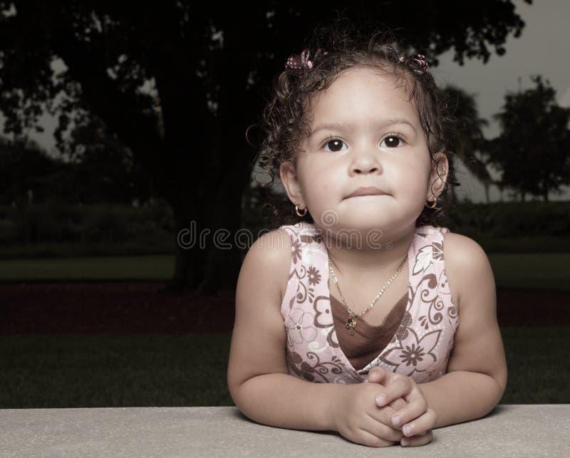 Criança nova que inclina-se em seus cotovelos foto de stock