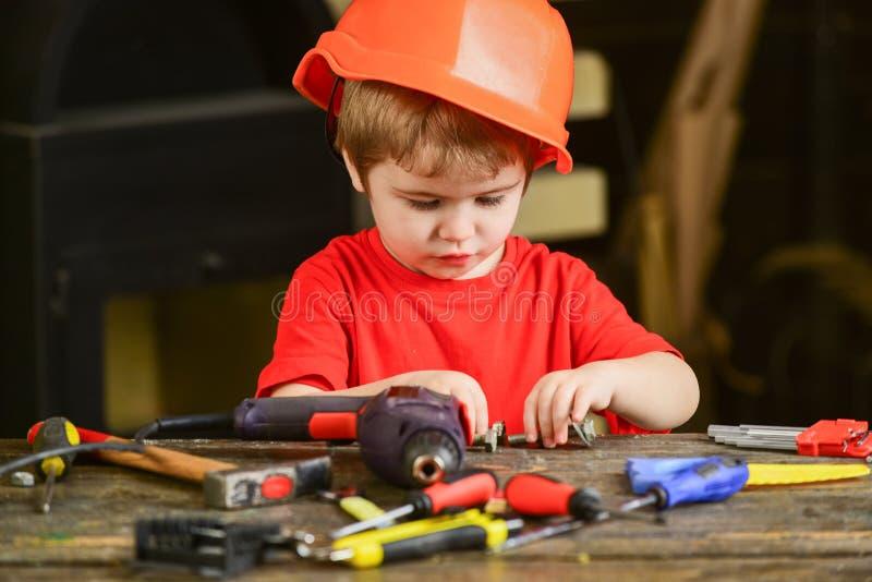 Criança ocupada que joga com parafusos do metal Trabalhador pequeno que senta-se na tabela com chaves de fenda, broca, martelo e  fotos de stock royalty free