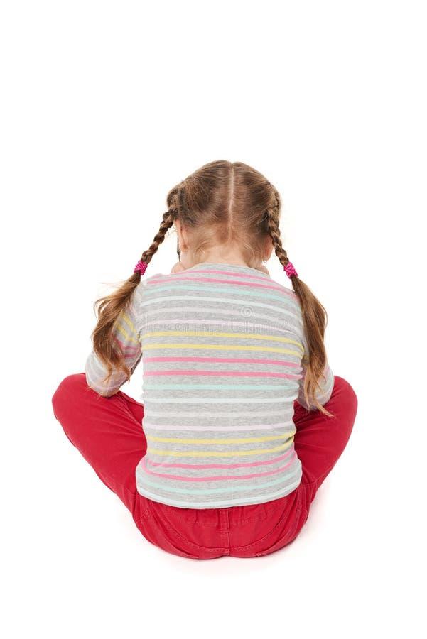 Criança ofendida que senta-se no assoalho, vista traseira imagem de stock royalty free