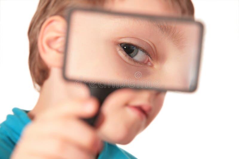 A criança olha através do magnifier imagem de stock