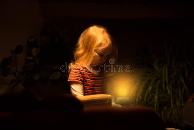 A criança olha dentro à luz da vela em uma sala escura foto de stock royalty free