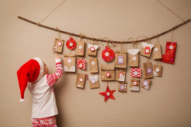 A criança olha o calendário do advento O bebê em um chapéu e em pijamas do Natal mostra no primeiro presente imagens de stock