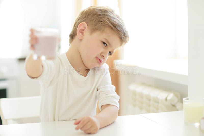 Criança ou menino feliz louro que comem na tabela Infância e felicidade, independência Café da manhã, manhã, família Menino peque fotografia de stock royalty free