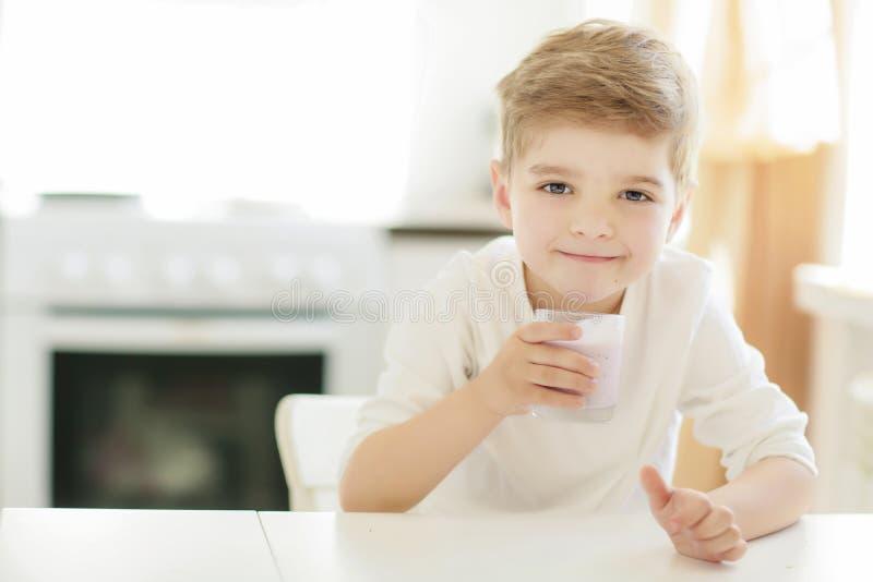 Criança ou menino feliz louro que comem na tabela Infância e felicidade, independência Café da manhã, manhã, família Menino peque fotografia de stock