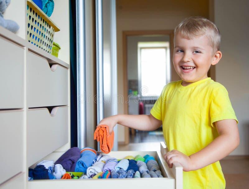 A criança põe sua roupa sobre O menino puxa o t-shirt fora de fotografia de stock royalty free