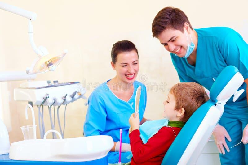 Criança, paciente que verifica o resultado do procedimento médico na clínica dental imagens de stock