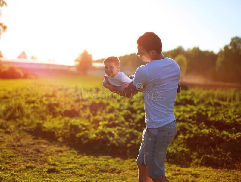 Criança, paizinho feliz e filho tendo o divertimento, guardando sobre as mãos imagens de stock
