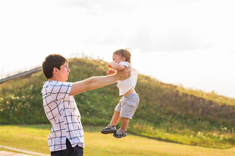 Criança, paizinho feliz e filho tendo o divertimento, guardando sobre as mãos em um fundo do por do sol da luz solar Família, cur fotos de stock