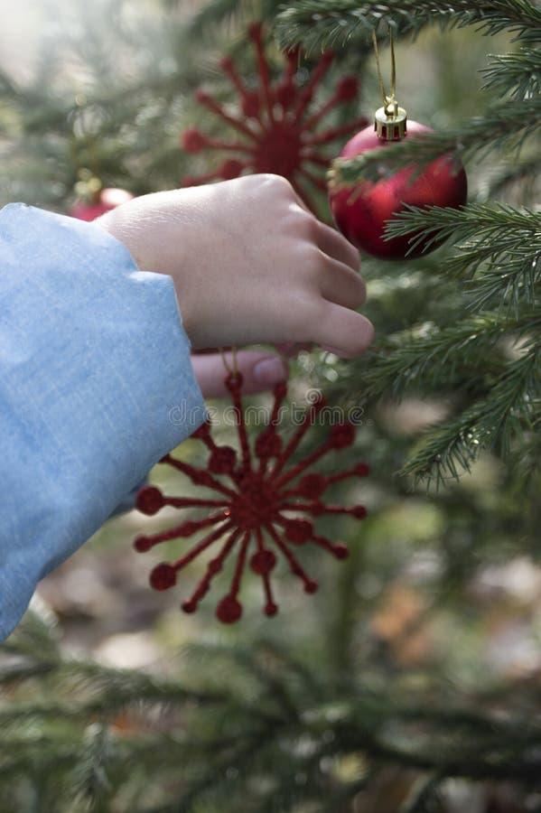A criança pendura um floco de neve do brinquedo do Natal na árvore de Natal, Natal imagens de stock