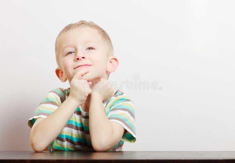 Criança pensativa pensativa loura da criança do menino do retrato na tabela interna imagem de stock royalty free