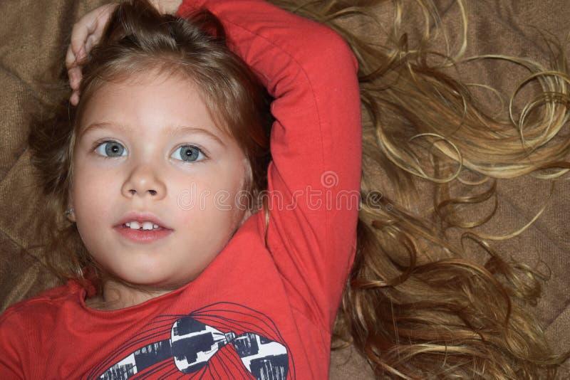 Criança pequena aberta seus olhos, rezando, sonhando no quarto imagens de stock