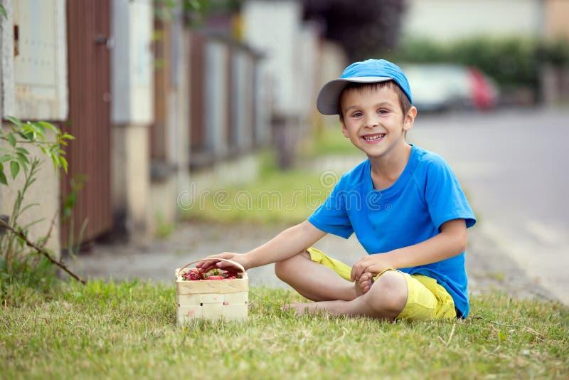 Criança pequena adorável doce, menino que come morangos, verão foto de stock