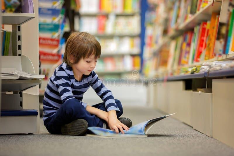 Criança pequena adorável, menino, sentando-se em umas livrarias foto de stock