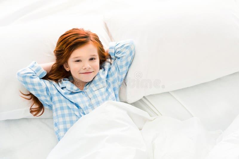 criança pequena adorável nos pijamas que encontram-se na cama e no sorriso foto de stock royalty free