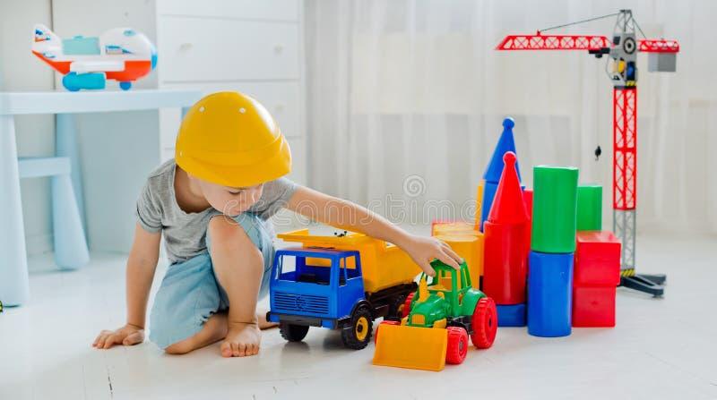 Criança pequena 4 anos velha, jogando com um grande número brinquedos plásticos coloridos na sala, construção de vário foto de stock royalty free