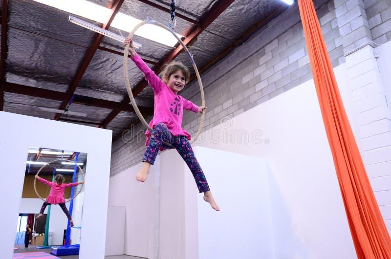 A criança pequena aprende habilidades do circo em Lyra aéreo imagens de stock royalty free