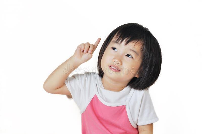 Criança pequena asiática da menina que aponta em algo fotografia de stock