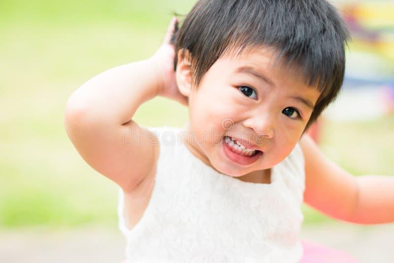 Criança pequena asiática que grita no fundo do campo de jogos imagens de stock