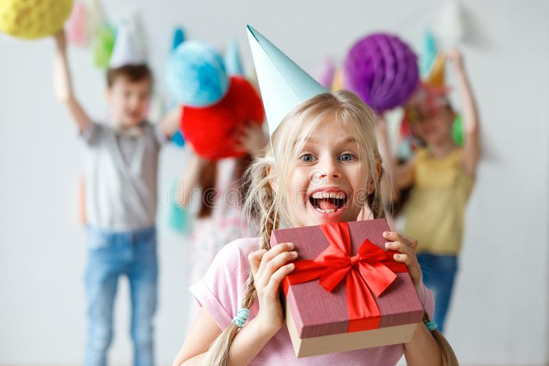 A criança pequena bonita de sorriso engraçada veste o chapéu do partido, abraça a caixa envolvida grande, contente de receber o p foto de stock