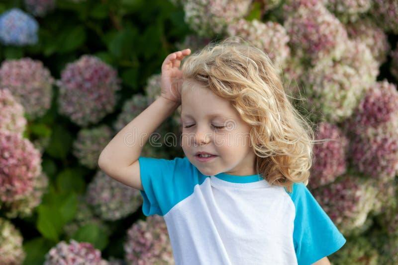 Criança pequena bonito com muitas flores no jardim fotografia de stock royalty free