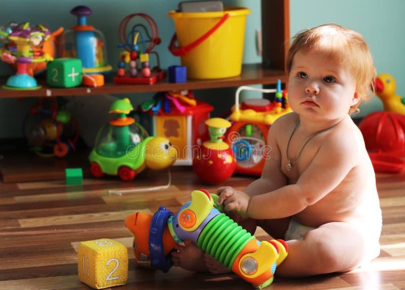Criança pequena bonito com o cabelo do gengibre que senta-se no assoalho entre fotos de stock royalty free