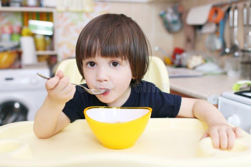 A criança pequena bonito come a sopa em casa imagem de stock