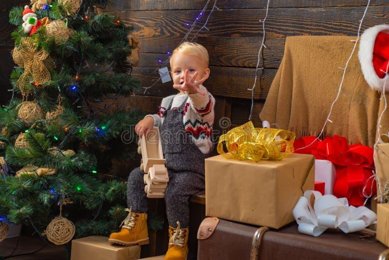 A criança pequena bonito está decorando a árvore de Natal dentro A criança aprecia o feriado Feliz Natal e ano novo feliz foto de stock royalty free