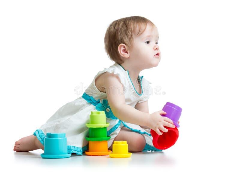 A criança pequena bonito está jogando com os brinquedos isolados imagem de stock