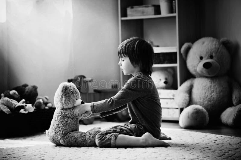 Criança pequena bonito, menino pré-escolar, jogando com o urso de peluche no hom fotografia de stock royalty free