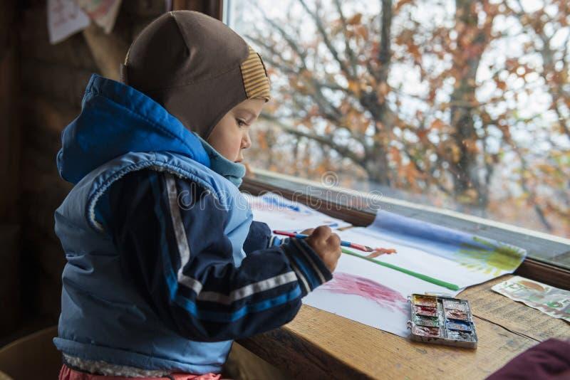 Criança pequena bonito na roupa morna com escova e pintura de pintura fotos de stock