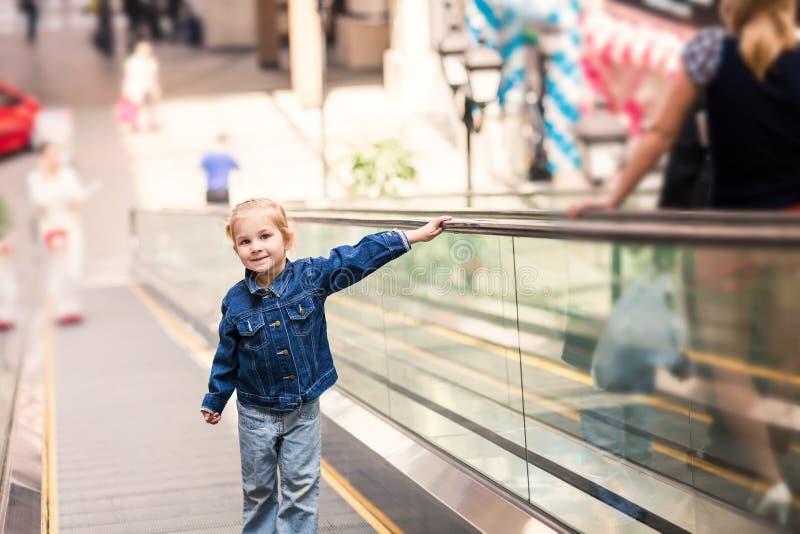 Criança pequena bonito no centro comercial que está em escada rolante movente imagens de stock royalty free