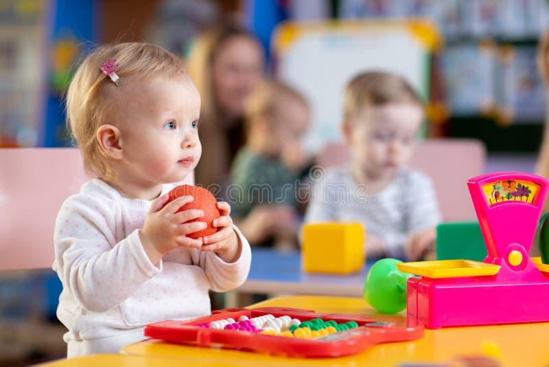Criança pequena bonito que joga com os brinquedos no berçário imagem de stock