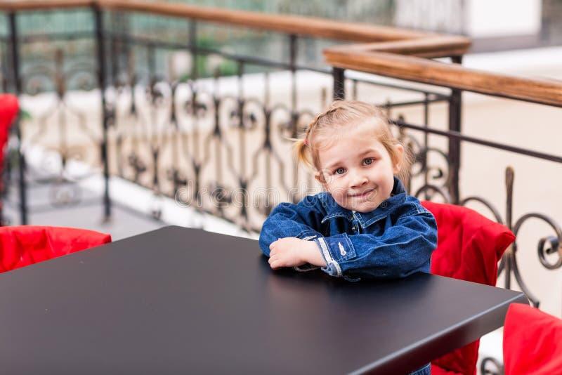 Criança pequena bonito que senta-se em um café no centro comercial imagens de stock