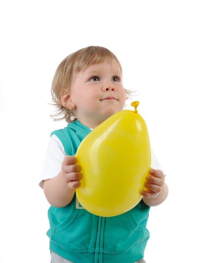 Criança pequena bonito que sorri e que prende um baloon foto de stock