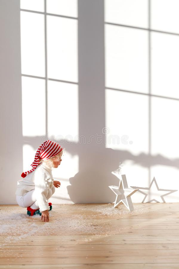 A criança pequena brincalhão veste o chapéu de Santa, jogos com neve artificial na sala espaçoso, olhares atentamente star, tem s foto de stock royalty free