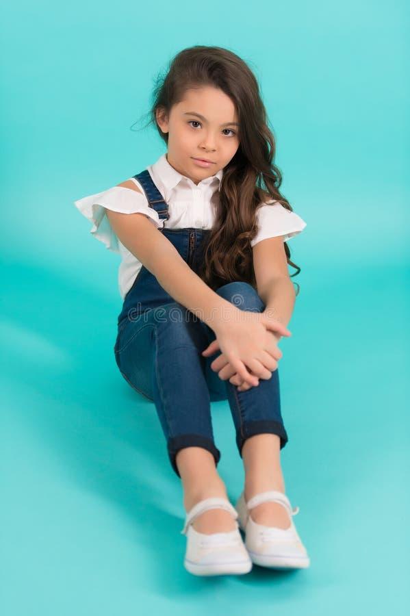 A criança pequena com cabelo longo nas calças de brim senta-se no assoalho imagem de stock royalty free