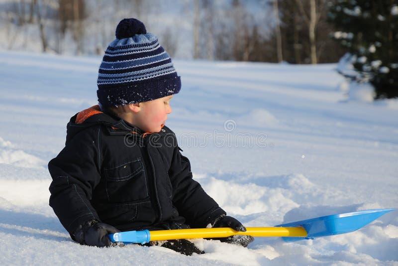 Criança pequena com a pá que senta-se na neve imagem de stock