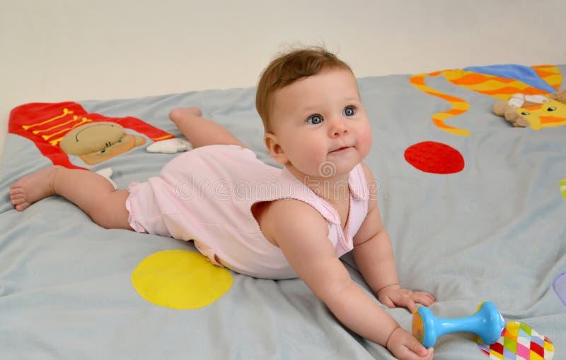 A criança pequena com um chocalho encontra-se em um estômago em um tapete do jogo fotos de stock royalty free