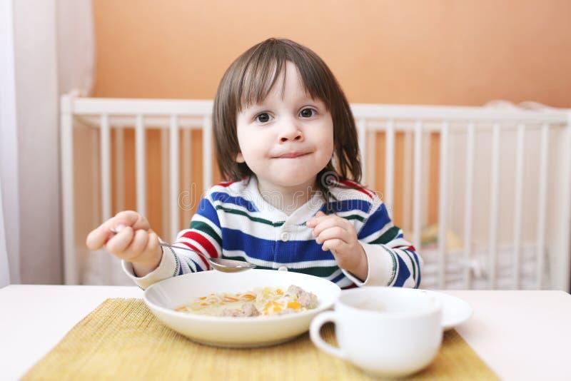 A criança pequena come a sopa foto de stock royalty free