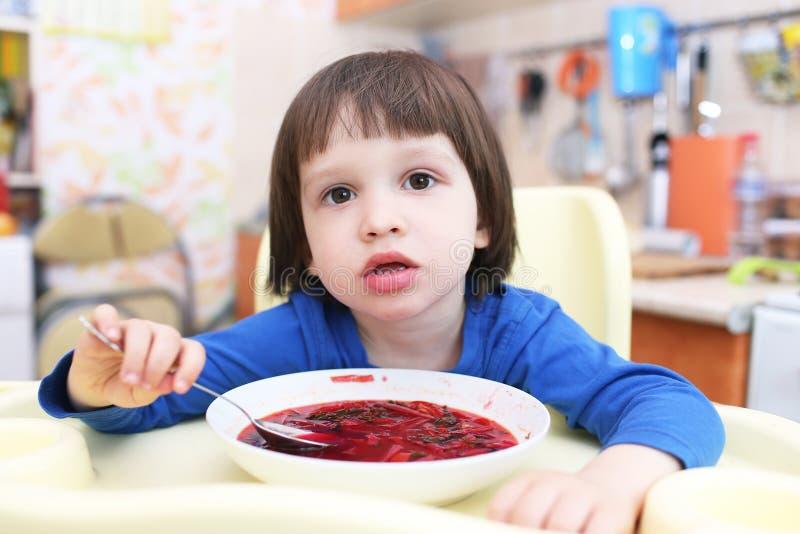 A criança pequena come a sopa vermelha saboroso foto de stock royalty free